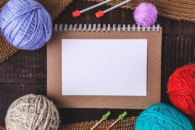 暗い背景に編み針、編み物用の明るい糸、ニット、茶色のスカーフ。上面図。コピースペース。編み物