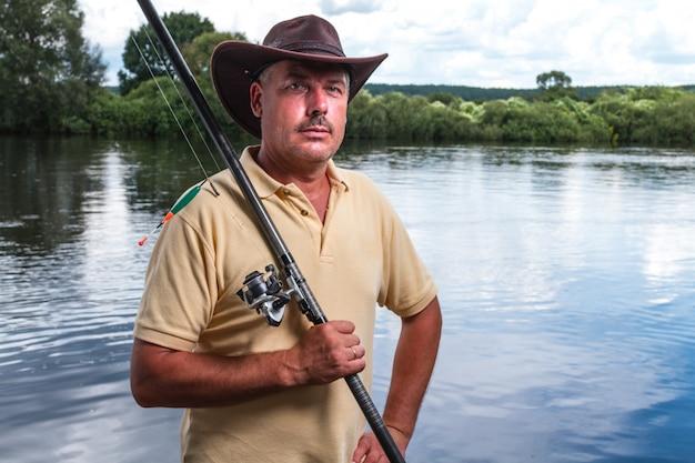 湖の背景に彼の肩に釣り竿を持つ漁師の肖像画。釣り。釣り道具
