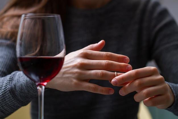 離婚した女性が指から結婚指輪を引っ張り、姦通、裏切り、失敗した結婚のために赤ワインを飲みます。離婚のコンセプト。関係と愛は終わります。人生の問題