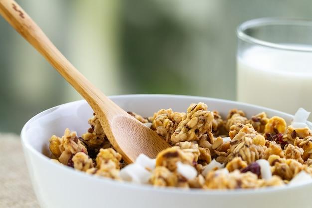 乾燥した朝食用シリアル。亜麻の種子、クランベリー、ココナッツ、牛乳のガラスとカリカリの蜂蜜グラノーラボウルをクローズアップ。健康で清潔な食物繊維