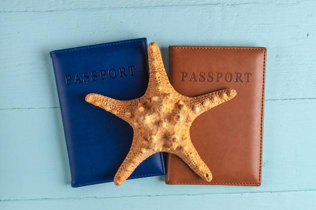 Путешествия, отдых, круиз. каникулы. паспорта, ракушки, морские звезды на синем, деревянный фон.