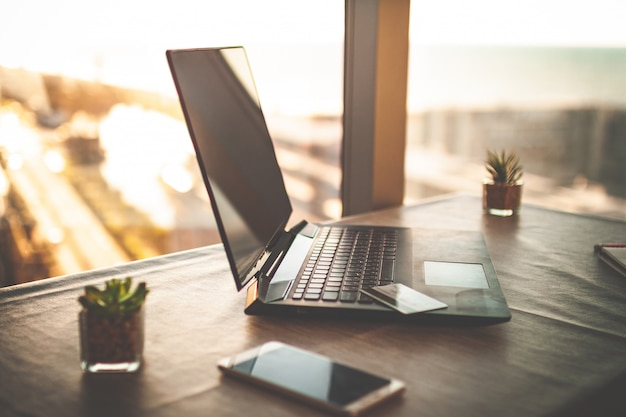 オンラインビジネス、作業、研究のための夕暮れ時の窓にテーブルの上のノートパソコンとホームオフィスで居心地の良い職場。リモートワーク