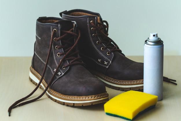 スポンジとスプレーでメンズスエードカジュアルブーツを身に着けています。靴磨き。履物の水分と汚れの保護