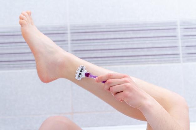 かみそりを使用して浴室の足を剃る女性をクローズアップ。自宅での美容トリートメント