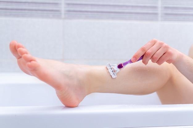 Женщина брить ноги в ванной комнате с помощью бритвы крупным планом. косметические процедуры в домашних условиях