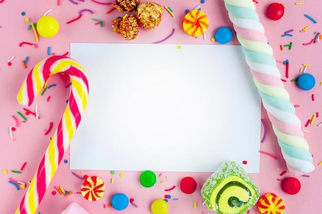異なる、砂糖、子供のお菓子の背景上のテキストのフレーム。ピンクの背景のお菓子。