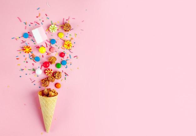 色付きのキャンディ、お菓子、マシュマロ、キャラメルポップコーン、ピンクの背景に甘い粉が付いているワッフルホーン。