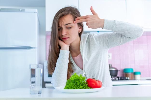 悲しい不幸な女性はダイエットにうんざりし、ダイエットで自分自身を根絶し、オーガニックで清潔な健康食品を食べざるを得ない