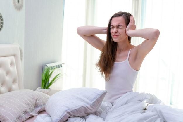 騒々しい隣人に苦しみ、邪魔され、早朝に自宅のベッドで寝ようとしている間に耳を手で覆う若い女性