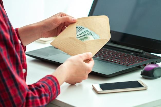従業員のオフィスは封筒にボーナスを受け取りました。違法な給与支払い
