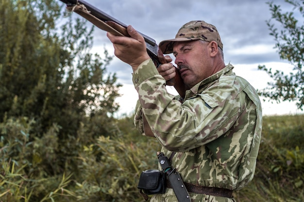 Охотник в форме с охотничьим ружьем. охота