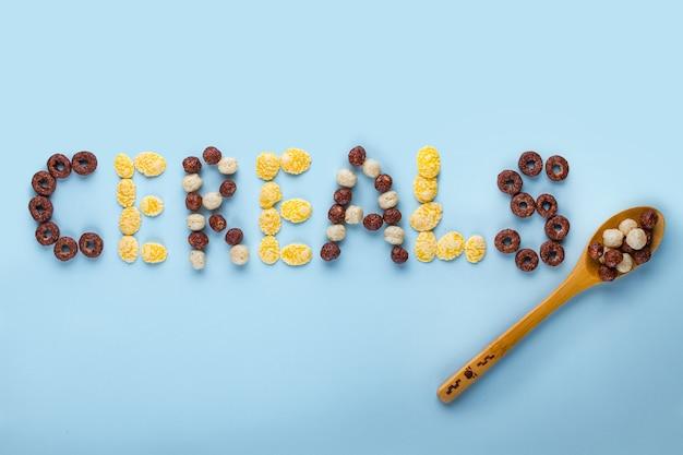 Концепция зерновых. ложка с глазированными, шоколадными шариками, кольцами и кукурузными хлопьями для здорового сухого завтрака на голубом поле