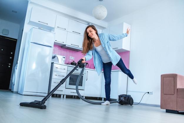 若い幸せな掃除人が掃除機を使用して家を掃除します。家事と清掃サービス。きれいなコンセプト