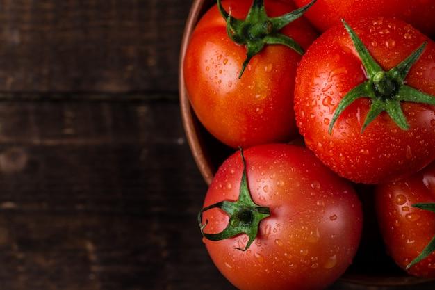 Свежие помидоры в тарелку на темном фоне крупным планом. сбор урожая помидоров. вид сверху