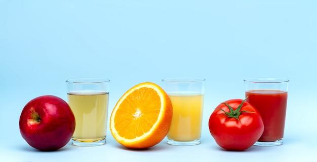 青いサーフに新鮮なオレンジ、リンゴ、トマトジュース。健康で自然な飲み物。食事とビタミン