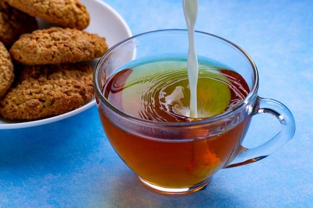 Завтрак с овсяным печеньем и наливанием молока в чашку черного чая. мука, крупа десертная и горячий напиток