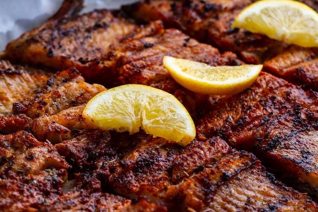 新鮮な魚のグリルテクスチャ。ジューシーなレモンのスライスとサーモンのグリル