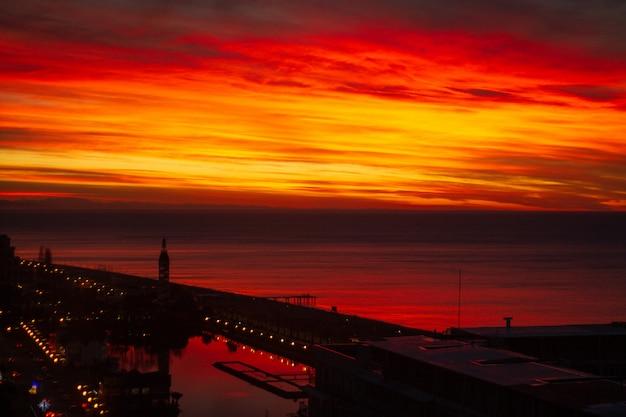 街の夜の素晴らしい、信じられないほどの美しい赤、ピンクの鮮やかな夕日の風景。夕焼け空のテクスチャと表面。美容自然
