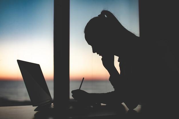 夕暮れ時のウィンドウに対してラップトップで遅く働くビジネスウーマンのシルエット。夜間および夜間のオンライン作業