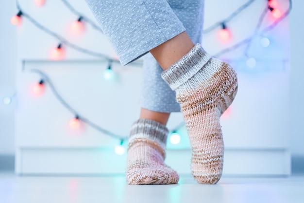 冬の自宅で暖かいニットの柔らかい居心地の良い靴下で女性の足。