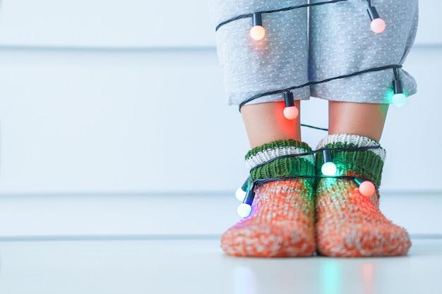 暖かいニットの柔らかい居心地の良いクリスマスの靴下と冬の自宅で照らされたライトとガーランドの女性の足。コピースペース