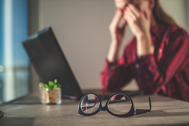Фрилансер чувствует усталость глаз и массирует глаза после долгого рабочего дня и использования ноутбука.