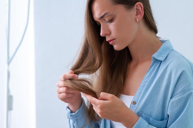 Портрет расстроен несчастной грустно женщина с поврежденной прядь волос, страдающих от сухих волос и секущихся кончиков.