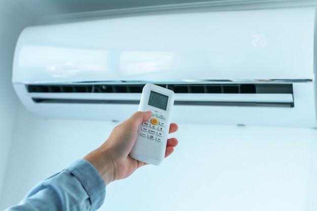 Регулировка температуры кондиционера с помощью пульта дистанционного управления в комнате дома.