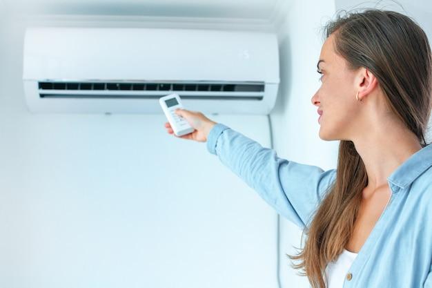 Молодая привлекательная женщина используя дистанционный регулятор для регулировки температуры кондиционера воздуха в комнате дома.