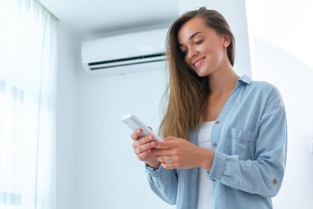 Молодая привлекательная женщина контролирует температуру кондиционера используя дистанционный регулятор в комнате дома.