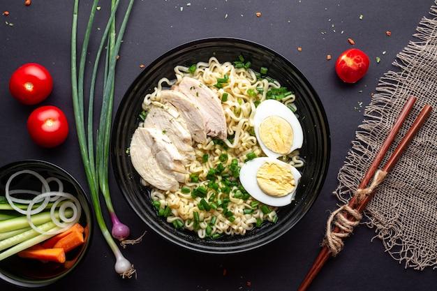 黒の背景に黒のボウルに鶏肉、野菜、卵入りのアジアのラーメン。上面図。