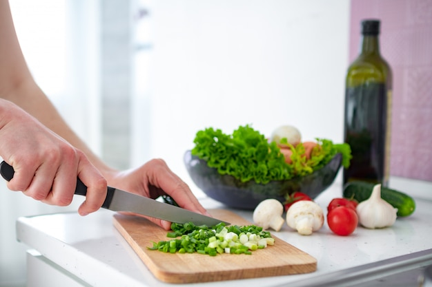 Нарезка овощей на разделочную доску для свежего салата на кухне дома
