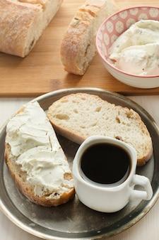 Вкусный завтрак с хлебом на мягком твороге и кофе.