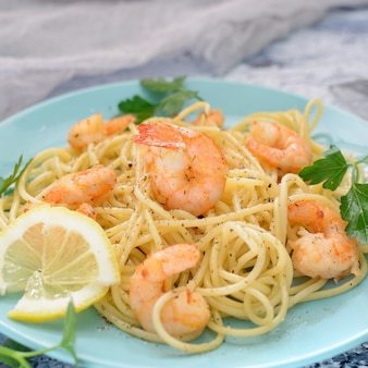 Спагетти с креветками на синих тарелках.