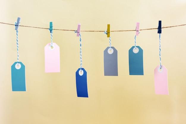 色の洗濯はさみでロープにぶら下がっているラベル