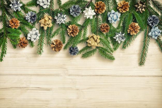 弓と円錐形で飾られたモミの枝の美しいクリスマスの組成