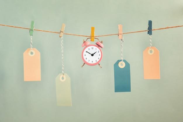 空のラベルと目覚まし時計がロープに掛かっています