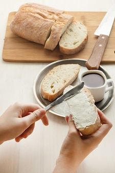 Человек намазывает на хлеб мягкие творожки