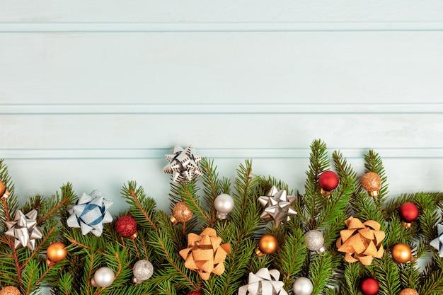 Рожденственский орнамент еловые ветки украшены разноцветными шариками и декоративными бантиками.