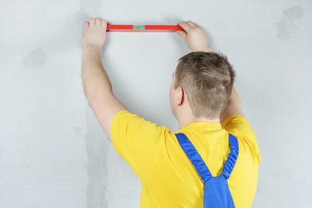 Ремонтник проверяет ровность стены, используя спиртовой уровень.