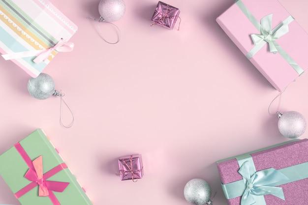 В центре светло-розовый фон, место для надписи, макет. вокруг сосновые шишки, новогодние шары и подарки.