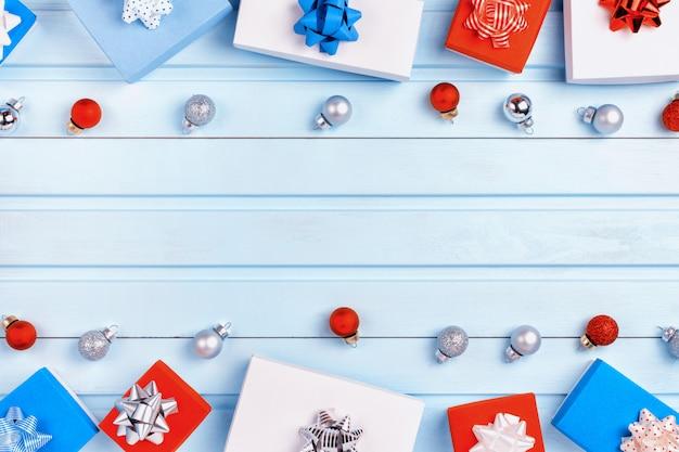 Рождественская композиция с копией пространства на голубом фоне. красные, синие и белые подарочные коробки с бантами и маленькими елочными шарами.