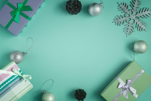На зеленом фоне лежат подарки, сосновые шишки и елочные шары. в центре есть пустое место для надписи, макет.