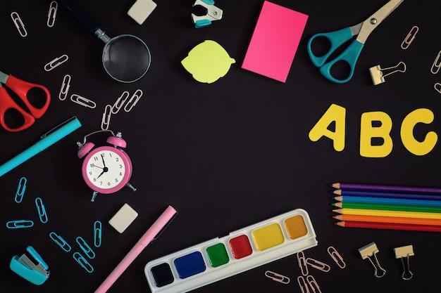 黒い背景には、色鉛筆、水彩絵の具、ハサミが円状に配置されています。中央には、テキスト用の空のスペースがあります。学用品は混乱しています。