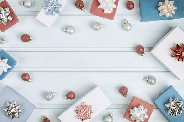 Рождественская композиция с копией пространства. в круге на синем фоне - красные и серебряные новогодние шары, подарочные коробки с бантами. праздничный макет.