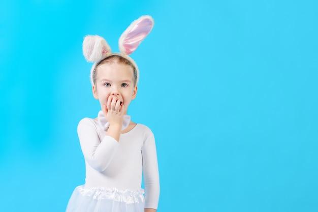 青い壁に白いウサギの衣装を着た子供。ウサギの耳を持つかわいい女の子は、驚きで彼女の口をカバーしています