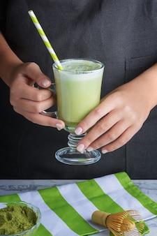 クローズアップ、女の子の手はガラスを保持しています。ストロー付きのグラスでは、緑茶の飲み物は子宮です。便利なラテ