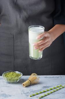 女の子は、フクロウのミルク入りの健康ドリンクを飲みながらグラスを手に持っています。抹茶ラテ。ベジタリアン製品