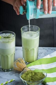 バリスタの女の子はグラスにミルクを加えます。健康ドリンクラテ緑茶抹茶。トリミングされた写真をクローズアップ
