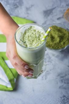 豆乳入りの健康ドリンク。緑茶から作られたラテは、クローズアップと一致します。ベジタリアン製品
